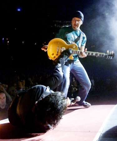 "U2 singer Bono (L) kicks The Edge's guitar during a sold-out stop of the band's Elevation Tour at the Thomas & Mack Center in Las Vegas November 18, 2001. The band is touring to support the album ""All That You Can't Leave Behind."" REUTERS Ethan Miller/Las Vegas Sun"