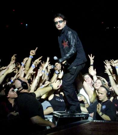 """'U2' singer Bono emerges from the crowd during a sold-out stop of the band's Elevation Tour at the Thomas & Mack Center in Las Vegas November 18, 2001. The band is touring to support the album """"All That You Can't Leave Behind."""" REUTERS/Ethan Miller/Las Vegas Sun"""