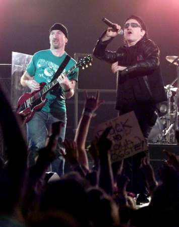 """U2 guitarist The Edge, (L), and singer Bono perform during a sold-out stop of the band's Elevation Tour at the Thomas & Mack Center in Las Vegas November 18, 2001. The band is touring to support the album """"All That You Can't Leave Behind."""" REUTERS Ethan Miller/Las Vegas Sun"""