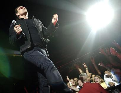 Bono of U2 walks past fans during a concert at the Staples Center in Los Angeles, Tuesday, April 5, 2005. (AP Photo/Chris Pizzello)